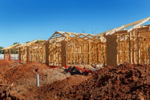 photo of houses in the middle of construction with wood frames and brown dirt su